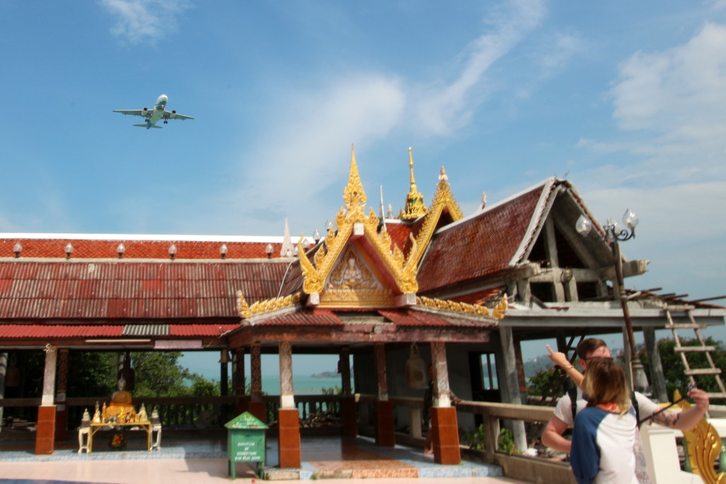 A plane flies over the temple
