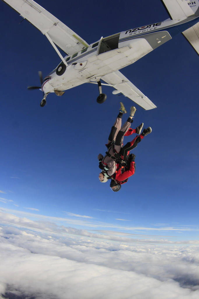 Alli falling headfirst out of the plane and into the air